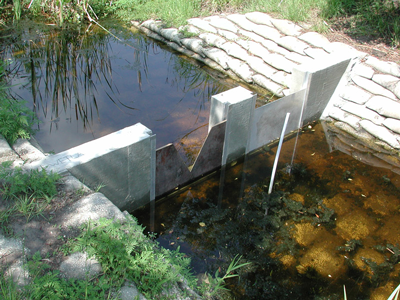 concrete wall spanning seepage channel with two stainless steel weir plates