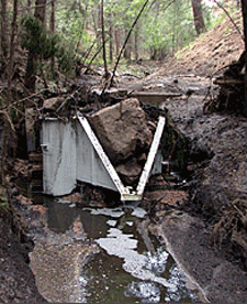 H flume with boulder lodged in the throat after a large rain event
