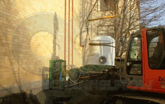 lowering a fiberglass Metering Manhole into excavation