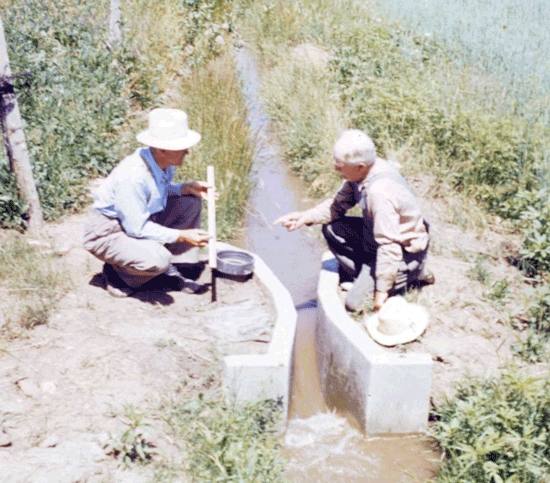 Dr. Ralph Parshall with farmer using concrete Parshall flume