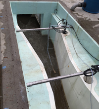 dual stilling wells on a fiberglass Parshall flume used to measure submerged flow