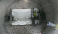 Trapezoidal flume grouted into a concrete manhole